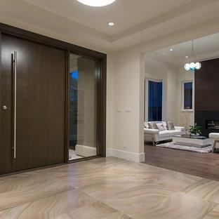 Inspiration för stora klassiska foajéer, med vita väggar, marmorgolv, en pivotdörr och mörk trädörr