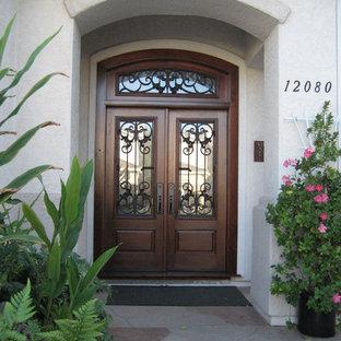 Cette image montre une porte d'entrée traditionnelle de taille moyenne avec un mur blanc, un sol en travertin, une porte double, une porte en bois foncé et un sol beige.