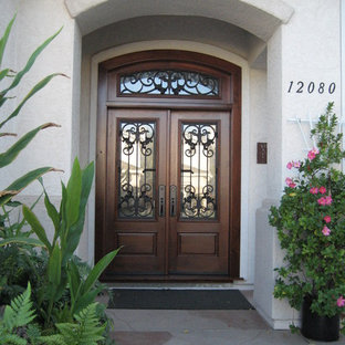 Example of a mid-sized classic travertine floor and beige floor entryway design in San Diego with white walls and a dark wood front door