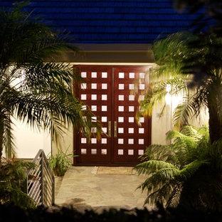 Exemple d'une porte d'entrée exotique de taille moyenne avec un mur blanc, un sol en travertin, une porte double, une porte en bois foncé et un sol beige.