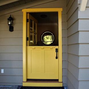 Cette image montre une petit porte d'entrée craftsman avec un mur gris, une porte hollandaise et une porte jaune.