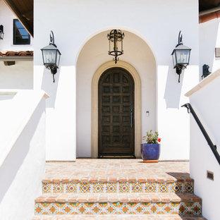 Diseño de puerta principal mediterránea con paredes blancas, suelo de ladrillo, puerta simple, puerta de madera oscura y suelo rojo