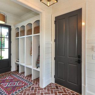 Пример оригинального дизайна: фойе в современном стиле с белыми стенами, кирпичным полом, одностворчатой входной дверью, серой входной дверью и красным полом
