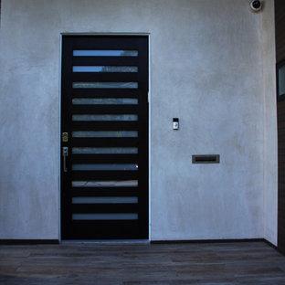 Inspiration pour une porte d'entrée minimaliste de taille moyenne avec un mur beige, un sol en bois clair, une porte simple et une porte en bois foncé.
