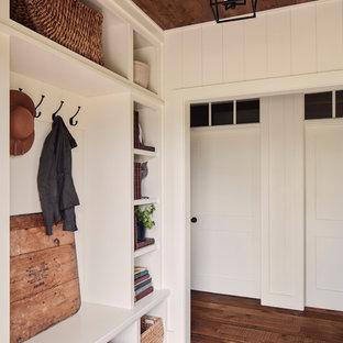 Exempel på ett lantligt kapprum, med vita väggar, mörkt trägolv och brunt golv