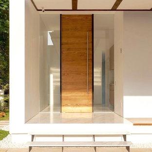 Modern inredning av en stor ingång och ytterdörr, med en pivotdörr, ljus trädörr, vita väggar, marmorgolv och vitt golv