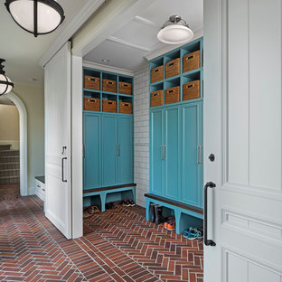 Example of a large classic brick floor and red floor mudroom design in Detroit with beige walls