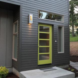 ポートランドの中くらいの片開きドアコンテンポラリースタイルのおしゃれな玄関ドア (グレーの壁、無垢フローリング、緑のドア) の写真
