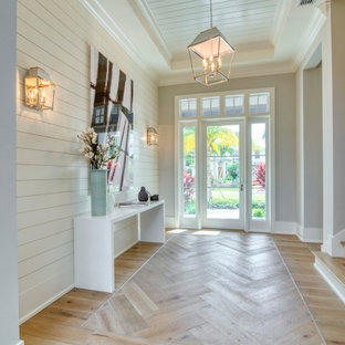 Example of a transitional medium tone wood floor, brown floor, shiplap ceiling, tray ceiling and shiplap wall entryway design in Miami with beige walls and a glass front door