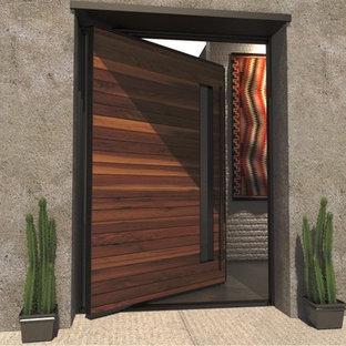 Пример оригинального дизайна: большая входная дверь в стиле модернизм с поворотной входной дверью и входной дверью из темного дерева