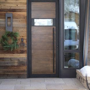На фото: маленькие входные двери в стиле модернизм с одностворчатой входной дверью, входной дверью из темного дерева и коричневыми стенами