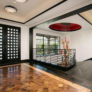 Exempel på en asiatisk entré, med vita väggar, bambugolv, en dubbeldörr och en svart dörr