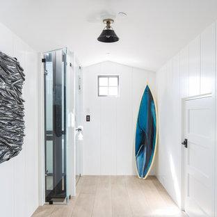 Foto de hall costero con paredes blancas, suelo de madera clara y suelo beige