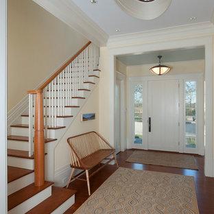 Cette image montre un hall d'entrée traditionnel avec un mur beige, un sol en bois brun, une porte simple et une porte blanche.
