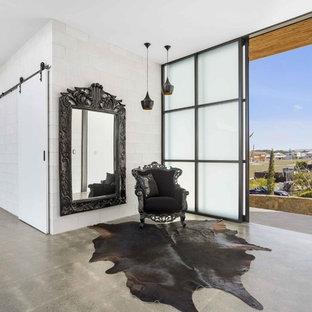Стильный дизайн: фойе в современном стиле с белыми стенами, бетонным полом, раздвижной входной дверью, стеклянной входной дверью и серым полом - последний тренд