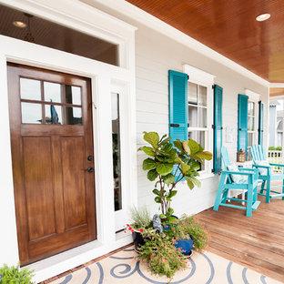 Modelo de puerta principal marinera con paredes grises, suelo de madera en tonos medios, puerta simple y puerta de madera en tonos medios