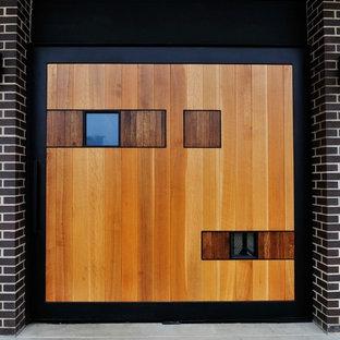Свежая идея для дизайна: входная дверь среднего размера в современном стиле с черными стенами, бетонным полом, двустворчатой входной дверью и входной дверью из дерева среднего тона - отличное фото интерьера