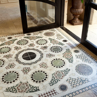 Example of a mid-sized tuscan limestone floor entryway design in Orange County with a glass front door