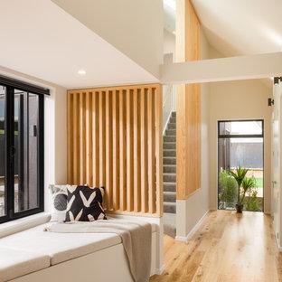 Modern inredning av en liten hall, med vita väggar, mellanmörkt trägolv och beiget golv