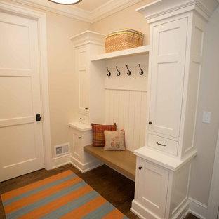 Idée de décoration pour une entrée tradition de taille moyenne avec un vestiaire, un mur beige, un sol en bois foncé, une porte simple et une porte blanche.