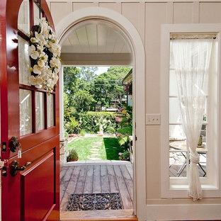 シアトルの中くらいのダッチドアトラディショナルスタイルのおしゃれな玄関ロビー (ベージュの壁、淡色無垢フローリング、赤いドア) の写真