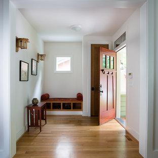 Cette image montre un hall d'entrée craftsman de taille moyenne avec une porte simple, une porte en bois foncé, un sol en bois brun, un mur blanc et un sol marron.