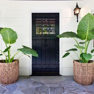 ロサンゼルスの片開きドアトロピカルスタイルのおしゃれな玄関ドア (黒いドア) の写真