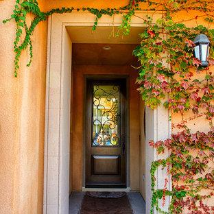 Idéer för att renovera en stor medelhavsstil ingång och ytterdörr, med orange väggar, en enkeldörr och mörk trädörr
