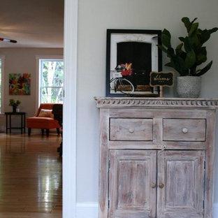 Réalisation d'un petit hall d'entrée tradition avec un mur beige, un sol en carrelage de céramique et un sol beige.