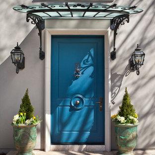 Ejemplo de puerta principal clásica, grande, con puerta simple, puerta azul y paredes grises
