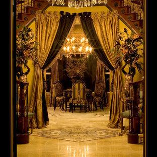 ロサンゼルスの巨大な両開きドア地中海スタイルのおしゃれな玄関 (メタリックの壁、トラバーチンの床、黒いドア) の写真