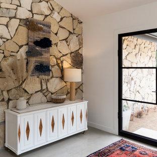 Cette image montre un hall d'entrée design avec béton au sol, une porte double, une porte en verre, un sol gris et un plafond voûté.