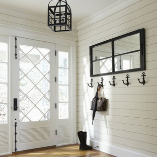 Example of a mid-sized coastal medium tone wood floor entryway design in Toronto with white walls and a glass front door