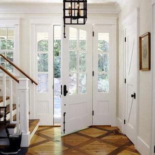 Aménagement d'un hall d'entrée sud-ouest américain de taille moyenne avec un mur blanc, un sol en bois brun, une porte simple et une porte en verre.