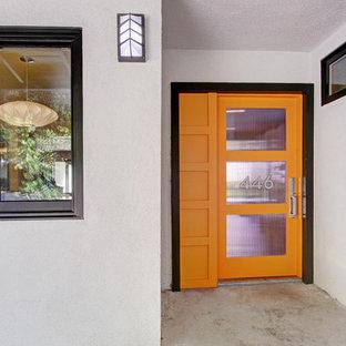 Esempio di una porta d'ingresso minimalista con pareti bianche, pavimento in cemento, una porta singola e una porta arancione