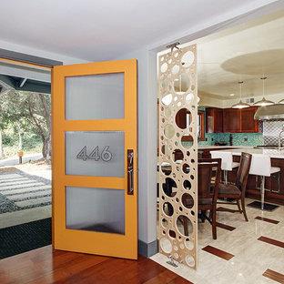 Modelo de puerta principal retro con paredes blancas, suelo de cemento, puerta simple y puerta naranja