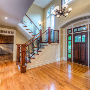 Photo of a large arts and crafts foyer in New York with beige walls, medium hardwood floors, a single front door, a dark wood front door and brown floor.