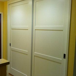 サンフランシスコの中サイズのコンテンポラリースタイルのおしゃれな玄関ホール (黄色い壁、トラバーチンの床、白いドア) の写真