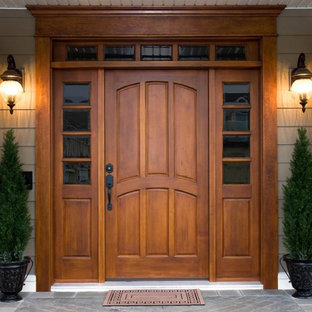 Large elegant entryway photo in Other with brown walls and a dark wood front door