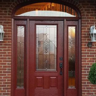 デトロイトの中くらいの片開きドアトラディショナルスタイルのおしゃれな玄関ドア (赤いドア、赤い壁、コンクリートの床) の写真