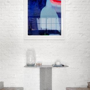 Bild på en stor funkis foajé, med vita väggar, travertin golv och beiget golv