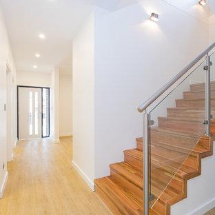 Bild på en funkis entré, med vita väggar, ljust trägolv, en enkeldörr, en vit dörr och gult golv