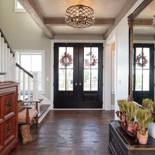 Cette image montre une entrée rustique avec un couloir, une porte double et du lambris de bois.