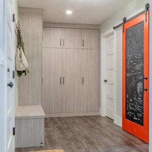 デンバーの片開きドアコンテンポラリースタイルのおしゃれなマッドルーム (グレーの壁、ラミネートの床、グレーの床、白いドア) の写真