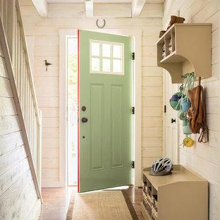 Modelo de puerta principal costera con paredes beige, suelo de madera en tonos medios, puerta simple y puerta verde