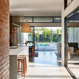 Стильный дизайн: большая узкая прихожая в современном стиле с белыми стенами, бетонным полом, одностворчатой входной дверью, черной входной дверью, серым полом и кирпичными стенами - последний тренд