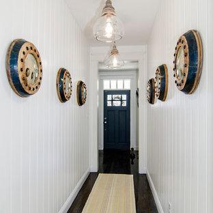 Diseño de hall marinero con paredes blancas, suelo de madera oscura, puerta simple y puerta negra