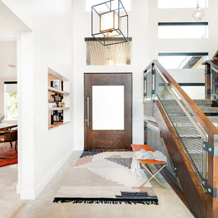 This is an example of a rustic foyer in Salt Lake City with white walls, a single front door and grey floors.
