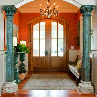 Idée de décoration pour une grand porte d'entrée style shabby chic avec un mur gris, une porte double, une porte en bois clair, un sol en bois brun et un sol marron.
