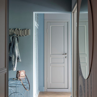 Inspiration for a small contemporary hallway in Moscow with blue walls, light hardwood flooring, a single front door, a white front door and brown floors.